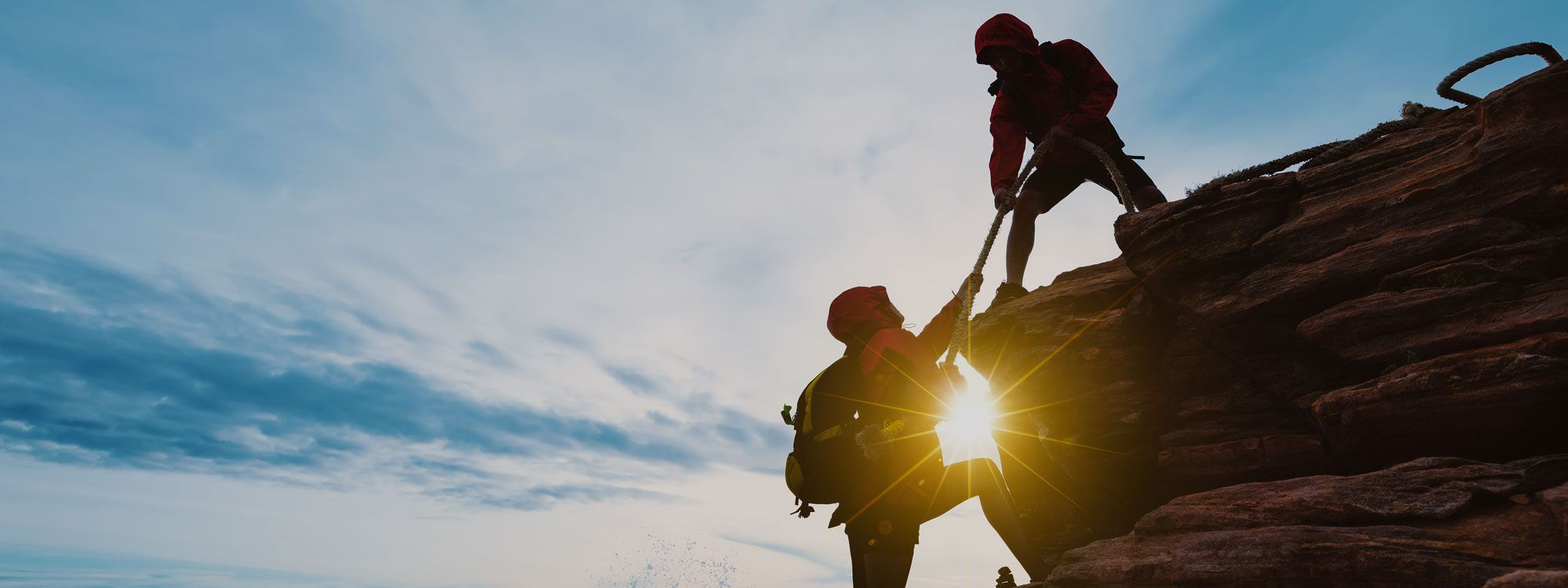 Climbers helping each other up mountain